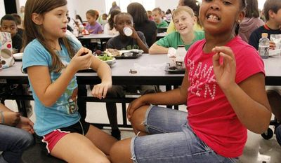 Eastside Elementary school fourth grader Raela Bridges (right) explains what parts of the school lunch she likes to her classmates Grace Bethany (left), Cameron Kinard (back left), and Brock Maddox (back right) on Sept. 12, 2012, in Clinton, Miss. (Associated Press)