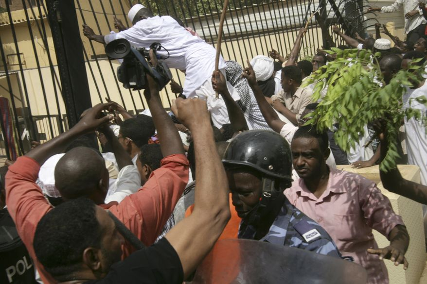 Sudanese protesters and riot police face off during a protest outside the German embassy in Khartoum, Sudan, Friday, Sept. 14, 2012, as part of widespread anger across the Muslim world about a film ridiculing Islam's Prophet Muhammad. Germany's Foreign Minister says the country's embassy in the Sudanese capital of Khartoum has been stormed by protesters and set partially on fire. Minister Guido Westerwelle told reporters that the demonstrators are apparently protesting against an anti-Islam film produced in the United States that denigrates the Prophet Muhammad.(AP Photo/Abd Raouf)