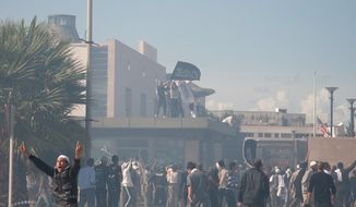 **FILE** Protesters gather in front of the main entrance of the U.S. embassy, background, in Tunis, Tunisia, on Sept. 14, 2012. Thousands of demonstrators massed outside the embassy and several were seen climbing the outer wall of the embassy grounds, an Associated Press reporter on the scene said. (Associated Press)