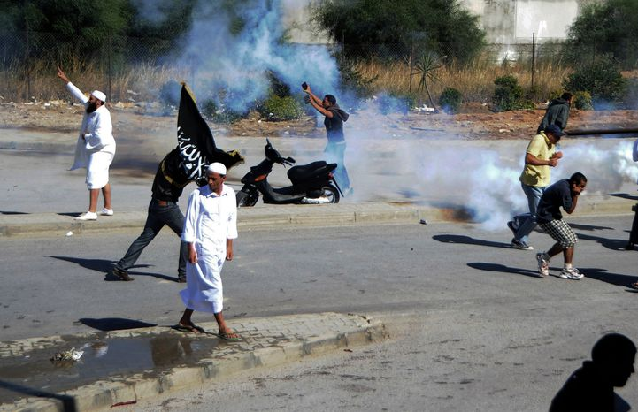 """Demonstrators throw stones Sept. 14, 2012, outside the U.S. Embassy in Tunis, Tunisia, during a protest against the anti-Islam film """"Innocence of Muslims"""" as police respond with tear gas. (Associated Press)"""