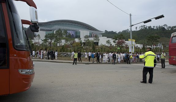 A police officer directs traffic outside the stadium at the Cheong Shim Peace World Center in Gapyeong, Korea on Saturday, Sept. 15, 2012, where hundreds of busloads of mourners arrived for the Seonghwa, or ascension, ceremony, known as the traditional funeral in western terms, for the late Rev. Sun Myung Moon. (Barbara L. Salisbury/The Washington Times)