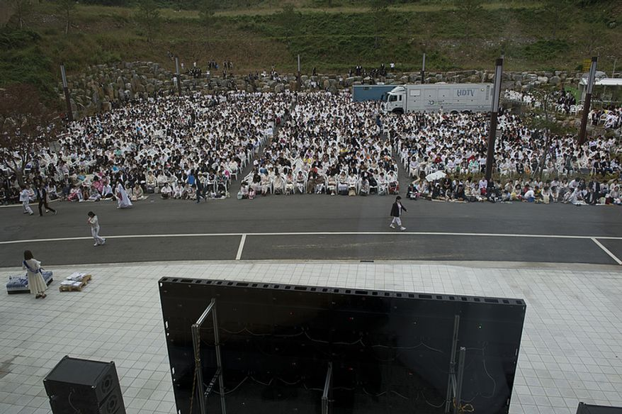 A huge crowd of mourners who could not make it into the stadium at the Cheong Shim Peace World Center to witness the Seonghwa, or ascension, ceremony for the late Rev. Sun Myung Moon on Saturday, Sept. 15, 2012 gather outside the building to watch the event live on a giant screen. The stadium holds about 15,000 people and was standing room only. (Barbara L. Salisbury/The Washington Times)