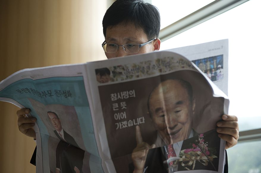 A man reads a paper that talks about the life of the late Rev. Sun Myung Moon in the stadium of the Cheong Shim Peace World Center in Gapyeong, Korea on Saturday, Sept. 15, 2012, the day of te reverend's funeral. (Barbara L. Salisbury/The Washington Times)