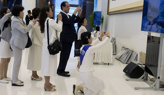 Mourners take pictures of a television screen showing the casket of the late Rev. Sun Myung Moon leave the palace to head to the stadium for the Seonghwa, or ascension, ceremony, known as the traditional funeral in western terms, on Saturday, Sept. 15, 2012 at the Cheong Shim Peace World Center in Gapyeong, Korea. (Barbara L. Salisbury/The Washington Times)