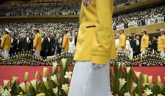 A group of second-generation family Unification Church members, dressed in yellow, process into the stadium at the Cheong Shim Peace World Center in Gapyeong, Korea on Saturday, Sept. 15, 2012 to line the walkway where the Rev. Sun Myung Moon's casket will make its way to the stage for the Seonghwa, or ascension, ceremony. (Barbara L. Salisbury/The Washington Times)