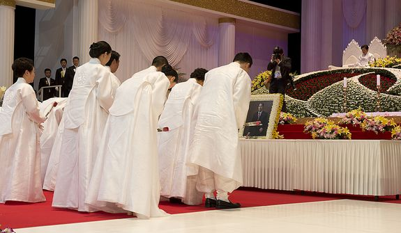 Family members of the late Rev. Sun Myung Moon bow after offering flowers before a portrait of the reverend during his funeral, called the Seonghwa, on Saturday, Sept. 15, 2012 at the Cheong Shim Peace World Center in Gapyeong, Korea. (Barbara L. Salisbury/The Washington Times)