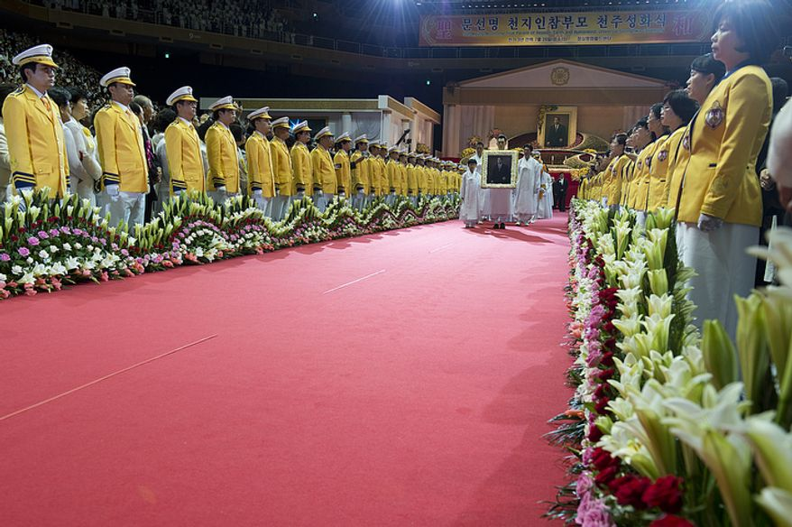 With members of second-generation Unification Church families lining the walkway in yellow, the family of the late Rev. Sun Myung Moon processes out of the stadium at the Cheong Shim Peace World Center in Gapyeong, Korea at the end of his funeral on Saturday, Sept. 15, 2012. (Barbara L. Salisbury/The Washington Times)