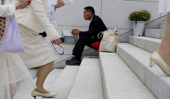 A man sits on the stairs outside the stadium at the Cheong Shim Peace World Center in Gapyeong, Korea on Saturday, Sept. 15, 2012 while female mourners, dressed in white, as is the tradition in Korean culture, walk up the steps for the funeral service for the late Rev. Sun Myung Moon. (Barbara L. Salisbury/The Washington Times)