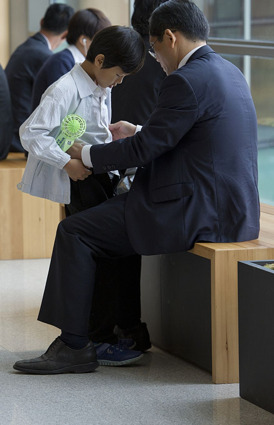 A father adjusts his son's clothes out in the hallway of the stadium at the Cheong Shim Peace World Center in Gapyeong, Korea before the funeral service for the late Rev. Sun Myung Moon on Saturday, Sept. 15, 2012. (Barbara L. Salisbury/The Washington Times)