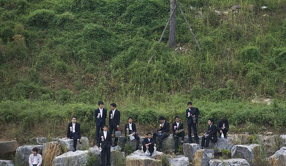 Young men and boys who could not get into the stadium to witness the late Rev. Sun Myung Moon's funeral in person sit on rocks outside to watch it on a large screen. The funeral was held Saturday, Sept. 15, 2012 at the Cheong Shim Peace World Center in Gapyeong, Korea. (Barbara L. Salisbury/The Washington Times)