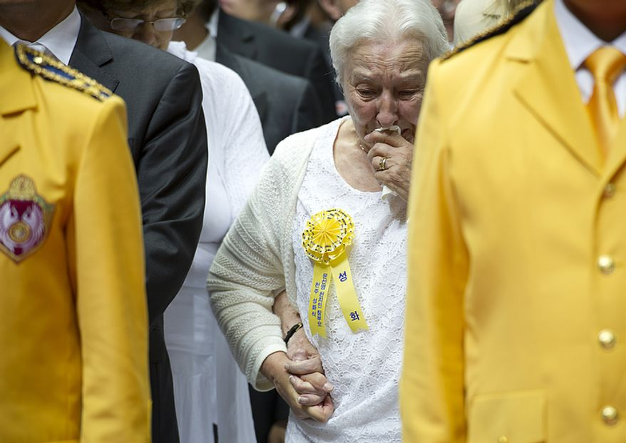 A woman cries as the casket enters the room during the funeral for the late Rev. Sun Myung Moon at the Cheong Shim Peace World Center in Gapyeong, Korea on Saturday, Sept. 15, 2012. (Barbara L. Salisbury/The Washington Times)