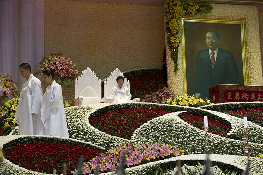 """At left, Hyung Jin Moon, son of the late Rev. Sun Myung Moon, and his wife exit the stage after lighting candles while Mrs. Moon sits in one of the chairs reserved for the """"True Parents"""" during the funeral service for her husband on Saturday, Sept. 15, 2012 at the Cheong Shim Peace World Center in Gapyeong, Korea. (Barbara L. Salisbury/The Washington Times)"""