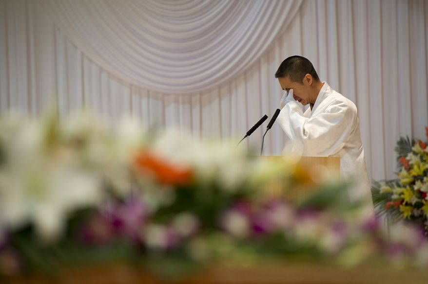 Hyung Jin Moon, son of the late Rev. Sun Myung Moon and new international president of the Unification Church, wipes his eyes while giving the Seonghwa address during his father's funeral on Saturday, Sept. 15, 2012 at the Cheong Shim Peace World Center in Gapyeong, Korea. (Barbara L. Salisbury/The Washington Times)