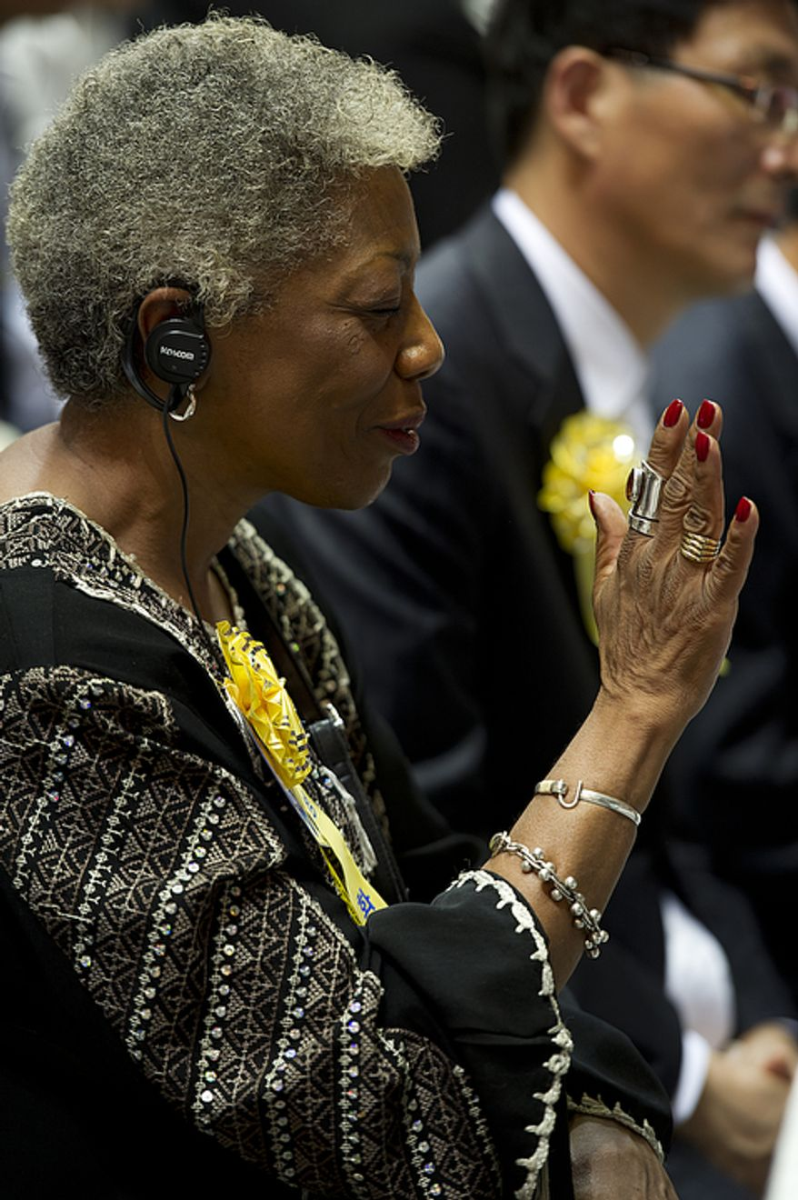 A woman holds up her hand in praise while listening to speakers during the funeral for the late Rev. Sun Myung Moon, held Saturday, Sept. 15, 2012 at the Cheong Shim Peace World Center in Gapyeong, Korea. (Barbara L. Salisbury/The Washington Times)