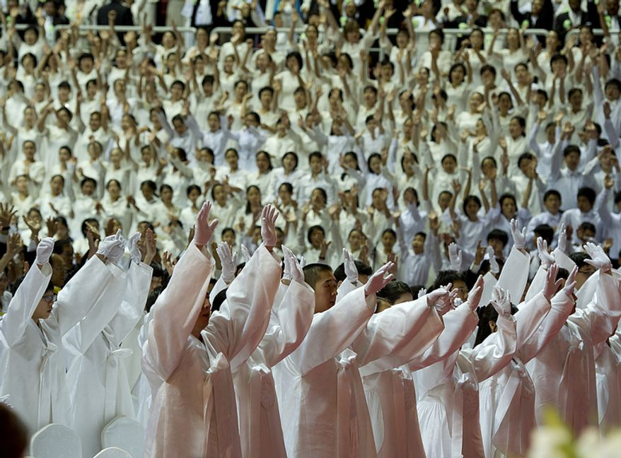 Family members and attendees raise their arms in the three cheers of EokMansei, a traditional Korean gesture, during the funeral for the late Rev. Sun Myung Moon on Saturday, Sept. 15, 2012 at the Cheong Shim Peace World Center in Gapyeong, Korea. (Barbara L. Salisbury/The Washington Times)