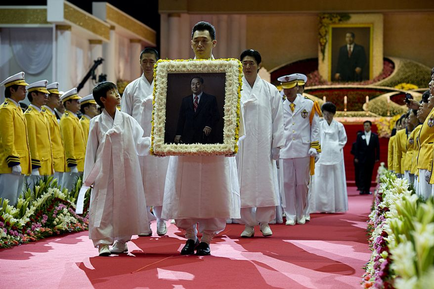 Members of the Moon family, including grandson Shin Jun, left, and Kwon Jin Moon, one of the sons of the late Rev. Sun Myung Moon, carrying a portrait of the reverend, process out of the stadium at the end of the Seonghwa, or ascension, ceremony, for the reverend Saturday, Sept. 15, 2012 at the Cheong Shim Peace World Center in Gapyeong, Korea. Lining the walkway in yellow are members of second-generation Unification Church families. (Barbara L. Salisbury/The Washington Times)
