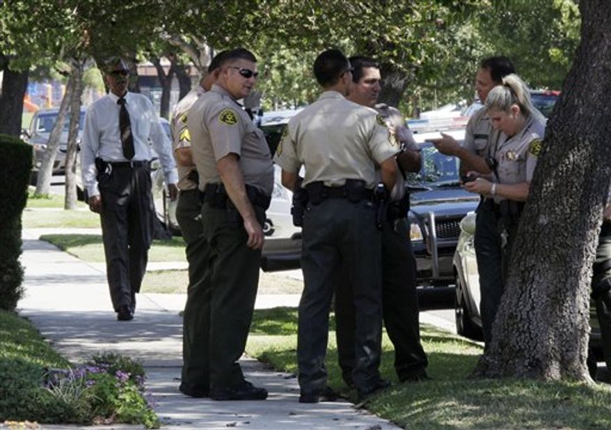 """Los Angeles County sheriff's deputies stand down the street from a suburban Los Angeles home believed to be that of filmmaker Nakoula Basseley Nakoula, Friday, Sept. 14, 2012. Federal authorities have identified Nakoula, a self-described Coptic Christian, as the key figure behind """"Innocence of Muslims,"""" a film denigrating Islam and the Prophet Muhammad that ignited mob violence against U.S. embassies across the Middle East. (AP Photo/Reed Saxon)"""