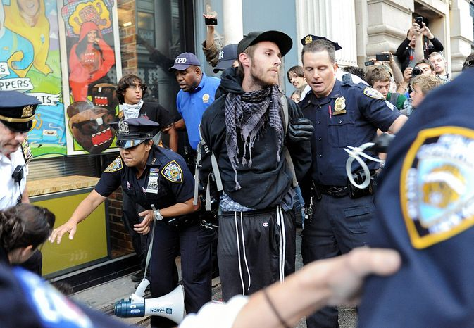 A person associated with Occupy Wall Street is arrested Saturday on a march along Broadway in New York en route to Zuccotti Park, where the social protest movement was born. Monday marks the one-year anniversary of the flagging effort. (Associated Press)
