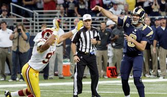 St. Louis Rams quarterback Sam Bradford, right, throws a touchdown pass to teammate Matthew Mulligan as Washington Redskins linebacker Lorenzo Alexander, left, defends during the fourth quarter of an NFL football game on Sunday, Sept. 16, 2012, in St. Louis. (AP Photo/Tom Gannam)
