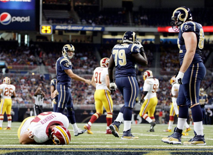 Redskins defensive end Adam Carriker lies on the field after suffering a knee injury just 21 seconds into Washington's game at St. Louis on Sunday. Linebacker Brian Orakpo injured his shoulder minutes later. (Associated Press)