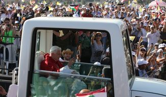 Pope Benedict XVI waves to the crowd from his popemobile upon his arrival to celebrate an open-air Mass for hundreds of thousands on the waterfront of Beirut on Sunday, Sept. 16, 2012. (AP Photo/Hussein Malla)