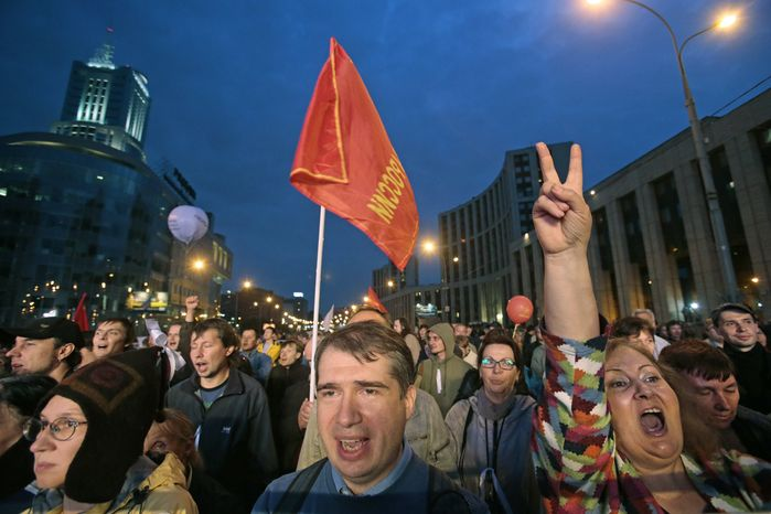 Opposition protesters react while listening to speakers during a rally in Moscow on Saturday, Sept. 15, 2012. The first major protest against President Vladimir Putin after a summer lull drew tens of thousands of people, determined to show that opposition sentiment remains strong despite Kremlin efforts to muzzle dissent. (AP Photo/Mikhail Metzel)