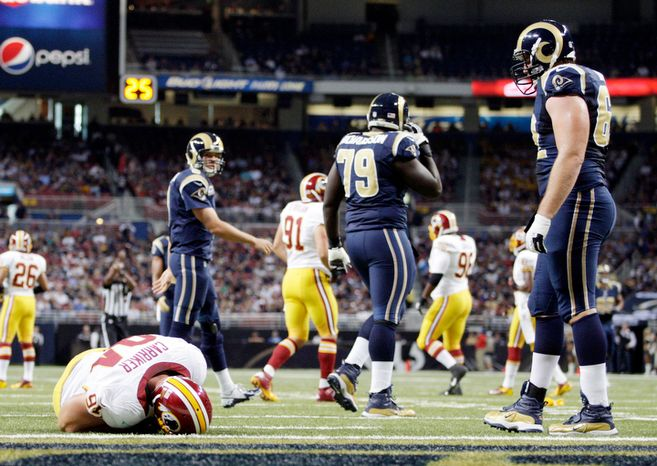 Washington Redskins defensive end Adam Carriker lies on the field after being injured during the first quarter of an NFL football game against the St. Louis Rams. (Associated Press)
