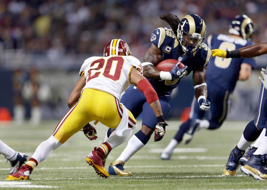 St. Louis Rams running back Steven Jackson, right, runs with the ball as Washington Redskins defensive back Cedric Griffin defends during the first quarter. (AP Photo/Jeff Roberson)