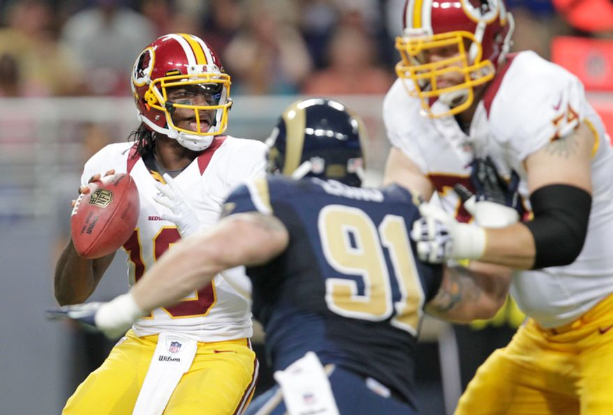 Washington Redskins quarterback Robert Griffin III looks to pass during the first quarter of an NFL football game against the St. Louis Rams. (AP Photo/Tom Gannam)