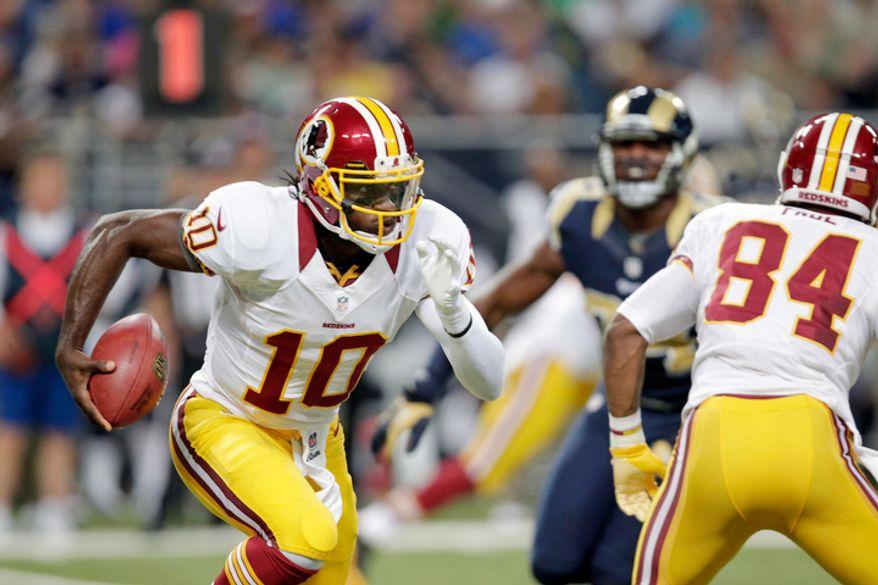 Washington Redskins quarterback Robert Griffin III runs with the ball during the first quarter. (AP Photo/Tom Gannam)
