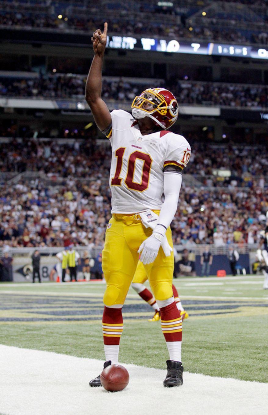 Washington Redskins quarterback Robert Griffin III celebrates after scoring on a 5-yard run during the first quarter. (AP Photo/Seth Perlman)