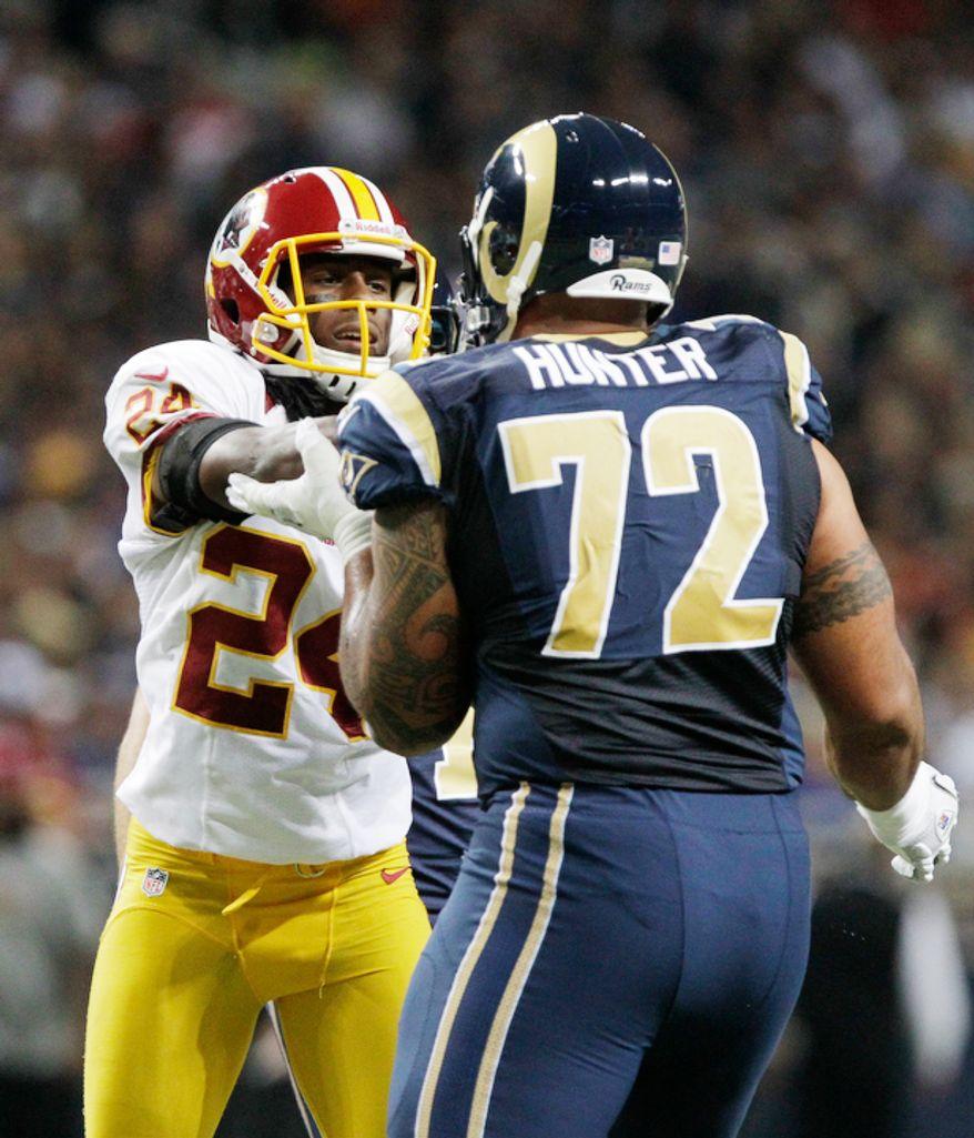 Washington Redskins strong safety DeJon Gomes, left, and St. Louis Rams tackle Wayne Hunter exchange shoves during the second quarter. (AP Photo/Seth Perlman)