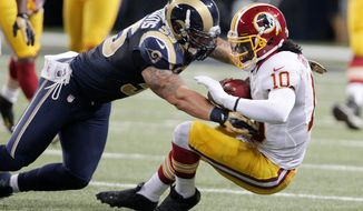 Washington Redskins quarterback Robert Griffin III, right, is hit by St. Louis Rams linebacker James Laurinaitis after running for a gain during the second quarter. (AP Photo/Tom Gannam)