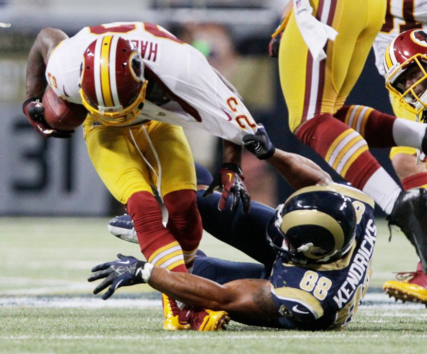 Washington Redskins cornerback DeAngelo Hall, left, recovers a fumble as St. Louis Rams tight end Lance Kendricks tries to pull him down during the fourth quarter. (AP Photo/Seth Perlman)