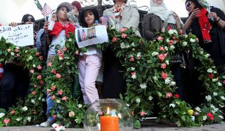 Libyans and Americans stand with wreaths, a poster and a photo of U.S. Ambassador J. Christopher Stevens on it as they gather on Monday in front of the U.S. consulate gate to pay their respect to Mr. Stevens and three other Americans killed in last week's attack on the consulate in Benghazi, Libya. (Associated Press)