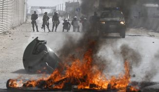 Afghan police stand by burning tires during a protest in Kabul, Afghanistan, Monday, Sept. 17, 2012. Hundreds of Afghans burned cars and threw rocks at a U.S. military base to protest an anti-Islam film that ridicules the Prophet Muhammad. (AP Photo/Ahmad Jamshid)