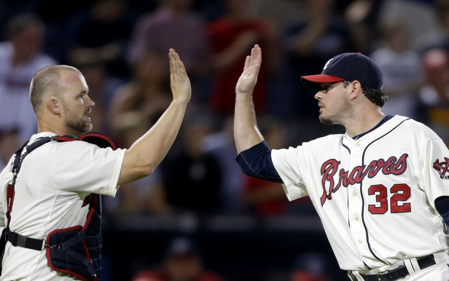 Atlanta Braves relief pitcher Chad Durbin, right, high-fives teammate David Ross, after the Braves defeated the Washington Nationals 5-1 in a baseball game Sunday, Sept. 16, 2012, in Atlanta. (AP Photo/David Goldman)