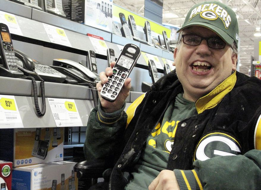 ** FILE ** Sean Irvin checks out cellphones at a Best Buy store in Anchorage, Alaska.(Associated Press)
