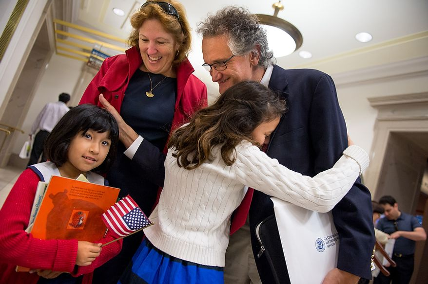 French native and D.C. resident Dominique Bagnato (right) is greeted by his wife, Tesa Conlin, and their two daughters Bliss Bagnato-Conlin (second from right), 11, and Mila Bagnato-Conlin, 7, after he and 224 others were sworn in as U.S. citizens on Sept. 17, 2012, at the National Archives Building in Washington, during a naturalization ceremony to commemorate the 225th anniversary of the signing of the U.S. Constitution. (Andrew Harnik/The Washington Times)