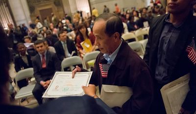 Duc Nguyen, originally from Vietnam, accepts his certificate of citizenship after being sworn in along with 224 others on Sept. 17, 2012, at the National Archives Building in Washington, during a naturalization ceremony to commemorate the 225th anniversary of the signing of the U.S. Constitution. (Andrew Harnik/The Washington Times)