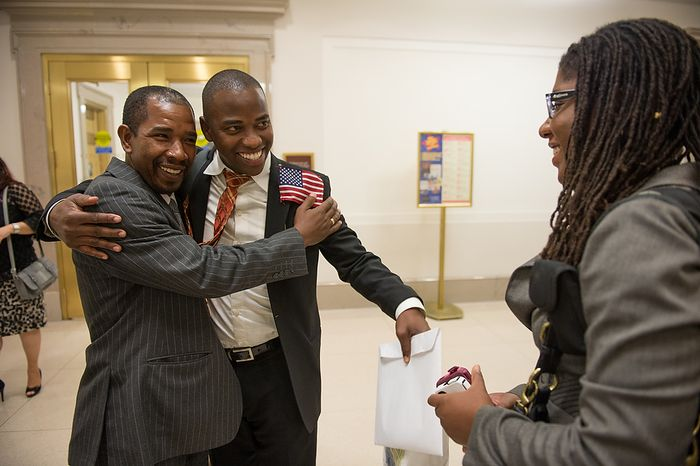 Oto Paz (left), originally from Colombia, hugs Julio Guity after both were sworn in as U.S. citizens Sept. 17, 2012, at the National Archives Building in Washington, during a naturalization ceremony to commemorate the 225th anniversary of the signing of the U.S. Constitution. (Andrew Harnik/The Washington Times)