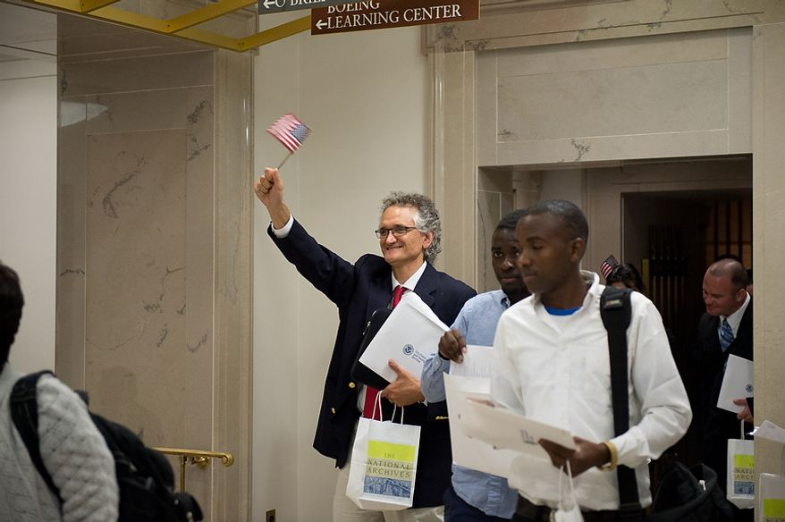 Dominique Bagnato (center), originally from France, waves a U.S. flag to his waiting family after he and 224 others were sworn in as U.S. citizens on Sept. 17, 2012, at the National Archives Building in Washington, during a naturalization ceremony to commemorate the 225th anniversary of the signing of the U.S. Constitution. (Andrew Harnik/The Washington Times)