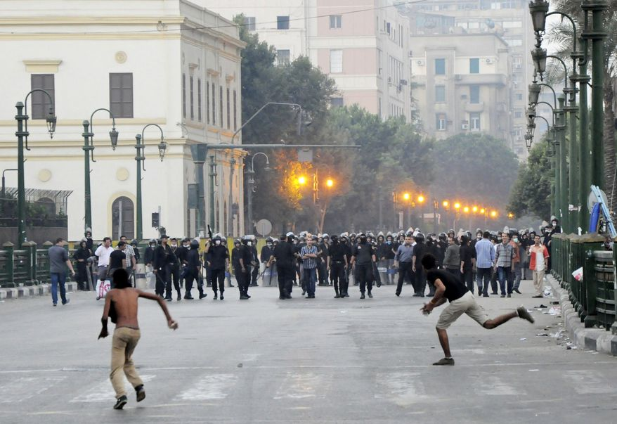 ** FILE ** Egyptian protesters hurl stones at riot police in downtown Cairo on Saturday, Sept. 15, 2012, before police cleared the area after days of demonstrations against a film ridiculing the Prophet Muhammad. (AP Photo)