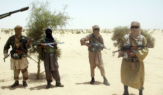 Fighters from Islamist group Ansar Dine stand guard during a hostage handover in the desert outside Timbuktu, Mali. Allied Islamist groups Ansar Dine and the Movement for Unity and Jihad in West Africa, or MUJAO, are applying strict Shariah justice across the northern half of Mali, which fell to the al-Qaeda-linked rebels. (Associated Press)