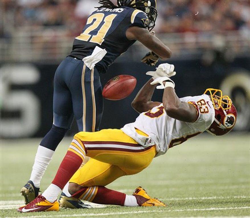 Fred Davis absorbs a helmet-to-helmet hit from Rams CB Janoris Jenkins / Associated Press
