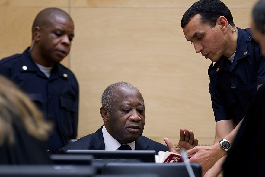Former Ivory Coast President Laurent Gbagbo (center) and security guards are seen as Mr. Gbagbo appears for the first time at the International Criminal Court in The Hague on Monday, Dec. 5, 2011, to face charges of crimes against humanity. (AP Photo/Peter Dejong, Pool)