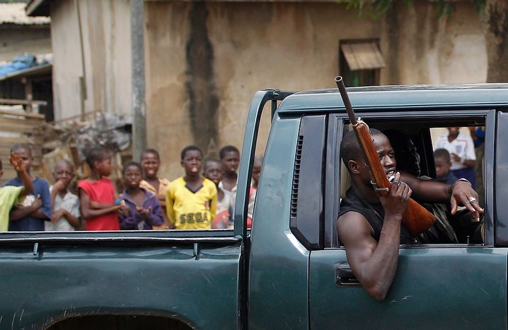 Children look on as a fighter opposed to Ivorian strongman Laurent Gbagbo passes in a pickup truck in the Anyama neighborhood of Abidjan, Ivory Coast, on Saturday, March 12, 2011. (AP Photo/Rebecca Blackwell)