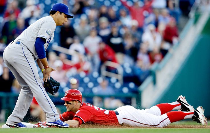 Washington Nationals' Bryce Harper slides safely into third for a triple as Los Angeles Dodgers third baseman Luis Cruz fields the throw during the fifth inning of the first baseball game of a doubleheader, Wednesday, Sept. 19, 2012, in Washington. The Nationals won 3-1. (AP Photo/Alex Brandon)