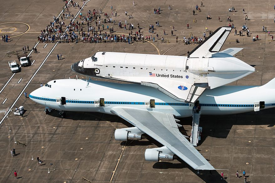 A crowd gathers around the space shuttle Endeavour, carried atop NASA's 747 Shuttle Carrier Aircraft, after landing at Ellington Field on Wednesday, Sept. 19, 2012, in Houston. Endeavour stopped in Houston on its way from the Kennedy Space Center to the California Science Center in Los Angeles, where it will be placed on permanent display. (AP Photo/Houston Chronicle, Smiley N. Pool, Pool)