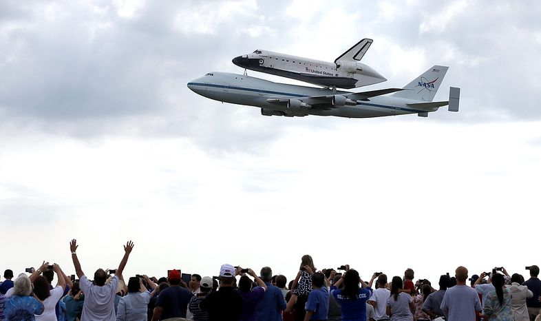 Space shuttle Endeavour flies over Ellington Field atop the shuttle aircraft carrier Wednesday, Sept. 19, 2012, in Houston. Endeavour is making a final trek across the country to the California Science Center in Los Angeles, where it will be permanently displayed. (AP Photo/David J. Phillip)